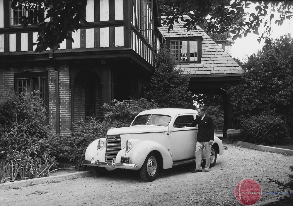 Studebaker President Paul G. Hoffman poses with a 1938 Studebaker Commander Coupe at his South Bend home. Hoffman's home later became Stanley Clark school.