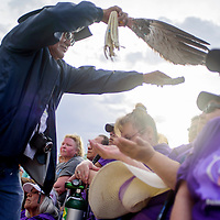 Don Yazzie uses eagle feathers to waft sage smoke over a crowd of cancer survivors for a traditional blessing during the annual Relay for Life Friday at the McKinley County Courthouse Plaza in Gallup.