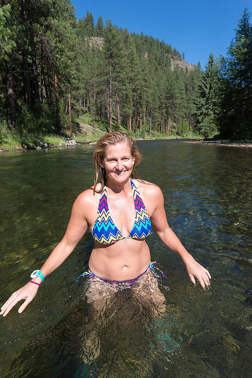 Woman standing in the Minam River, Wallowa Mountains, Oregon.