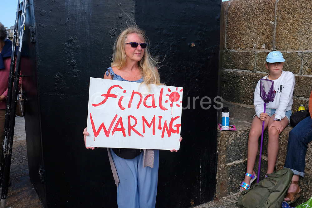 Climate change activists from the seaside town of St Ives in Cornwall gathered to protest at the lack of activity by the British Government on climate change on 31st August 2019, in St Ives, United Kingdom. The group, of Extinction Rebellion activists walked through the town of St Ives, United Kingdom. The group protested about rising sea levels caused by climate breakdown.  Extinction Rebellion are dedicated to illuminating the global environmental crisis and supporting groups and organisations fighting to save humanity and all species from mass extinction.<br /> Extinction Rebellion is a climate change group started in 2018 and has gained a huge following of people committed to peaceful protests. These protests are highlighting that the government is not doing enough to avoid catastrophic climate change and to demand the government take radical action to save the planet.