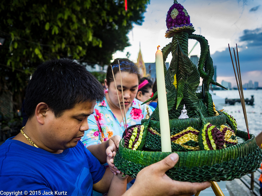 25 NOVEMBER 2015 - BANGKOK, THAILAND:  A Thai family prays before floating their krathong during Loy Krathong at Wat Yannawa in Bangkok. Loy Krathong takes place on the evening of the full moon of the 12th month in the traditional Thai lunar calendar. In the western calendar this usually falls in November. Loy means 'to float', while krathong refers to the usually lotus-shaped container which floats on the water. Traditional krathongs are made of the layers of the trunk of a banana tree or a spider lily plant. Now, many people use krathongs of baked bread which disintegrate in the water and feed the fish. A krathong is decorated with elaborately folded banana leaves, incense sticks, and a candle. A small coin is sometimes included as an offering to the river spirits. On the night of the full moon, Thais launch their krathong on a river, canal or a pond, making a wish as they do so.    PHOTO BY JACK KURTZ