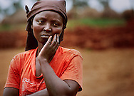 A Rwandan Hutu refugee woman listens as other refugees demand they receive food at the Keza refugee camp near Ngara, Tanzania. Most of the other residents of Keza had fled the previous night to avoid returning home to Rwanda.