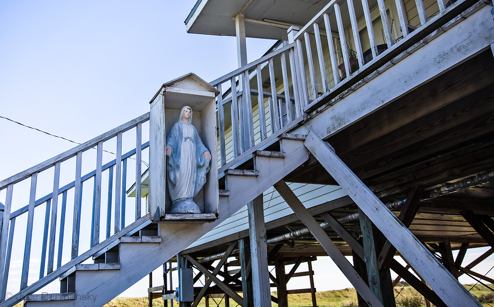 Statue of the Virgin Mary mounted on the staris of a raised home on the Isle de Jean Charles.