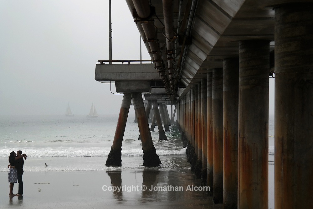 A couple embrace next to the Venice pier on a foggy fall Saturday afternoon