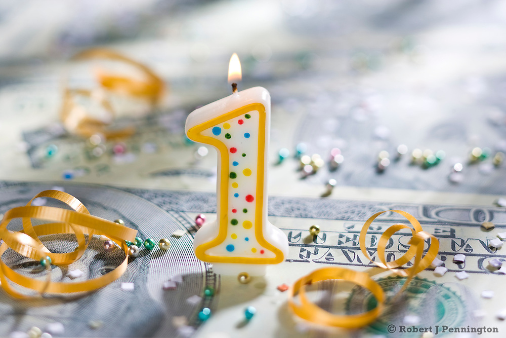 One (1) year  celebration candle on U.S. currency.