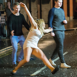 """© Licensed to London News Pictures . 20/12/2014 . Manchester , UK . A woman slips and falls on Bootle Street . """" Mad Friday """" revellers out in the rain and cold in Manchester . Mad Friday is typically the busiest day of the year for emergency services , taking place on the last Friday before Christmas when office Christmas parties and Christmas revellers enjoy a night out .  Photo credit : Joel Goodman/LNP"""