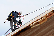 Shannon Wilson, a carpenter with Western Wood Structures and journeyman member of Local 1503, nails plywood to the inclined roof truss on PCC Sylvania's College Center building. Howard S. Wright is the general contractor on a bond-funded project to construct a new GBD Architects-designed entrance to the building.