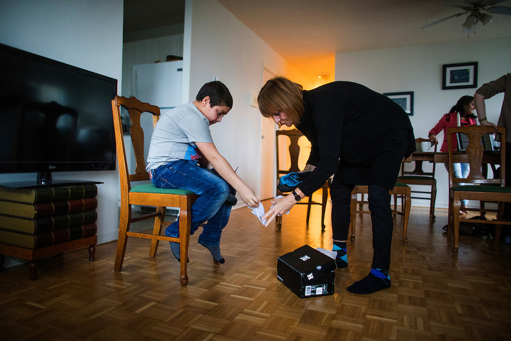 Syrian refugee sponsor Valerie Pringle helps refugee Nasimi Batal Al Hasan put on the new shoes she bought him inside their apartment in Mississauga, Ontario, Canada, Thursday January 21, 2016.   (Mark Blinch for the BBC)