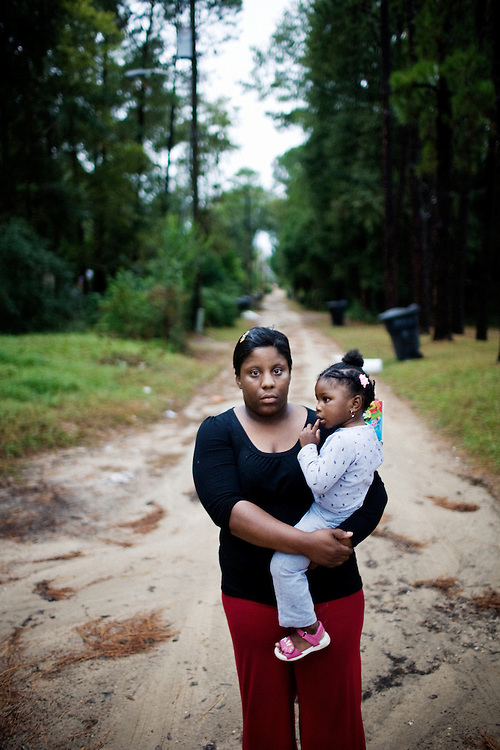 """Lettorea """"Lottie"""" Clark, 25 and her daughter Gabby, 2, outside their apartment in Albany, GA on Friday, October 24, 2008. Lottie and Gabby live off welfare after escaping an abusive relationship with Gabby's father."""