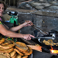 Woman Cooking Sausage Over Open Fire in Market in Nha Trang, Vietnam<br /> Nha Trang is a coastal city of about half a million people.  It is emerging as a popular tourist destination for its beaches. In recent years, it hosted the Miss Universe and Miss Earth pageants.  Tucked away from this progress, however, are areas that still cling to traditions.  An example is this woman who was cooking breaded sausages over an open flame in a market.