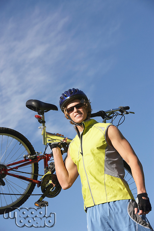Young man carrying bicycle, outdoors, portrait