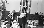 27/06/1963 - John F. Kennedy attends a garden party at Áras an Uachtaráin. A female casualty from the groups of people who swooned about Kennedy is carried away.