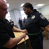 Terry Dahlem of Mid South Uniform and Equipment of Jackson measures Columbus Police Officer Latessa Fluker for a new bullet proff vest as areas officers get fitted at the Lee County Justice Center on Friday.