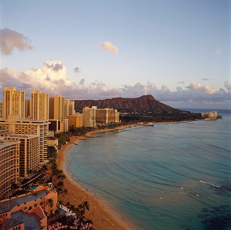 Waikiki Beach in Honolulu on the island of Oahu, Hawaii with a spectacular view of Diamond Head, the ocean at sunset and in the bottom, left hand corner of the photo, the Royal Hawaiian Hotel.