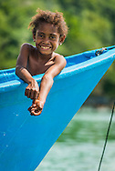 Raja Ampat, West Papua, Indonesia, December 2016. Papuan girls fishing from a boat. Yenanas Paradise home stay on the island of Gam. Thousands of small islands fringed by coral reefs and blue water mangroves litter the Raja Ampat archipelago. The turquoise and blue waters are teeming with marine life that forms the livelihood for the local Papuan population. Kayak4conservation is the Raja Ampat Research & Conservation Centre (RARCC) project that supports the locals to develop a community based, sustainable tourism project, inviting visitors to explore their islands by sea kayak with a local guide and experience the culture by staying amongst the local people in traditional style homestays. Photo by Frits Meyst / MeystPhoto.com