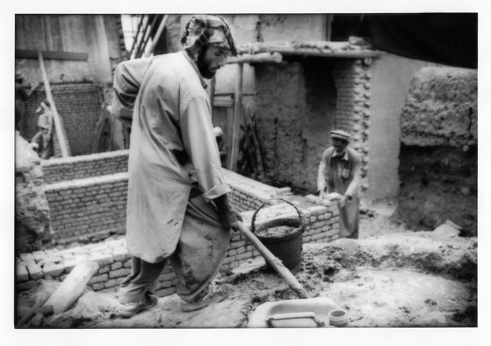 Local Kabuli man mixes mud used as mortar to rebuild a mudbrick wall within Murad Khane, Kabul, Afghanistan.  Turquoise Mountain Foundation, a non-profit organization, employs local men to help restore this neighborhood in the old city of Kabul.