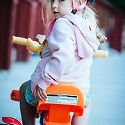 A toddler looks back at the camera while riding her big wheel tricycle.