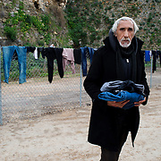 Greece with Doctors of the World (Medecins du monde). Chios Island, one of the places where refugees from Turkey land en route to Northern Europe. Souda camp. A newly arrived refugee with his clothes that have dried in the sun.