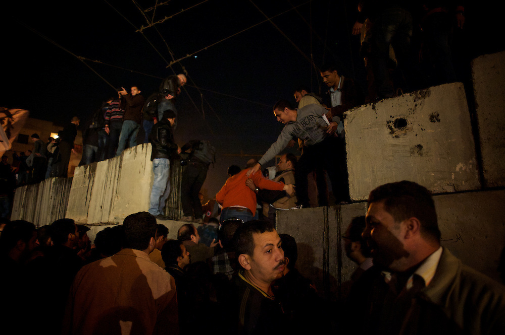 December 11, 2012 - Cairo, Egypt: Protestors stand on top of a concrete wall set up outside the presidential place in Cairo, where tens of thousands gathered to voice their anger at the planned constitution, which will be put to a referendum next Saturday...The Egyptian army has reportedly called talks between President Mohamed Morsi and the opposition to end violent protests against a draft constitution...Sporadic clashes between supporters and opponents of president Mohamed Morsi, erupted in the past week over his assumption of extraordinary powers and the scheduling of the referendum. (Paulo Nunes dos Santos/Polaris)
