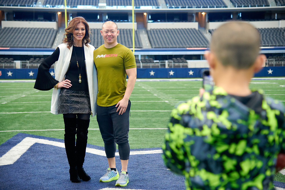 Charlotte Jones Anderson poses for a photo with a visitor on the football field at AT&T Stadium in Arlington, Texas on December 12, 2017. (Cooper Neill for The New York Times)