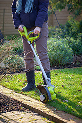 Using an electric grass edge trimmer to cut lawn edges