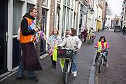 Een begeleider loopt met een groep schoolkinderen met takken voor palmpasen door Utrecht.<br /> <br /> A guide is walking with a group school children with branches for palm sunday.