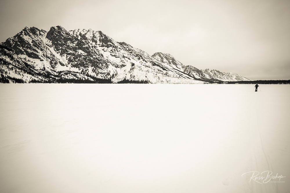 Backcountry skier crossing frozen Jenny Lake, Grand Teton National Park, Wyoming