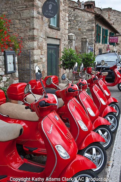 Red vespa motocycles, scooters, parked at a rental location, in Radda, in Chianti, Tuscany, Italy