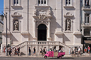 "A pink Tuk Tuk has stopped at a red light outside Igreja de Nossa Senhora do Loreto (church) during a city sightseeing tour through Praca Luis Camoes, on 11th July 2016, in Lisbon, Portugal. The company operating these vehicles is Turma das Ilusoes ""Organization of touristic and cultural activities, thematic tours, with or without advertising."" The Church of Loreto, is next to Largo do Chiado at the corner with Rua da Misericordia. With the Lisbon earthquake of 1755 the church suffered extensive damage and was rebuilt in 1785. (Photo by Richard Baker / In Pictures via Getty Images)"