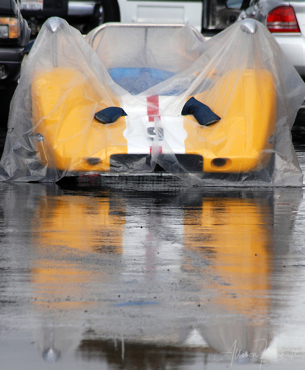 A racecar is protected from the rain while waiting for races to start during an HMSA event at Laguna Seca