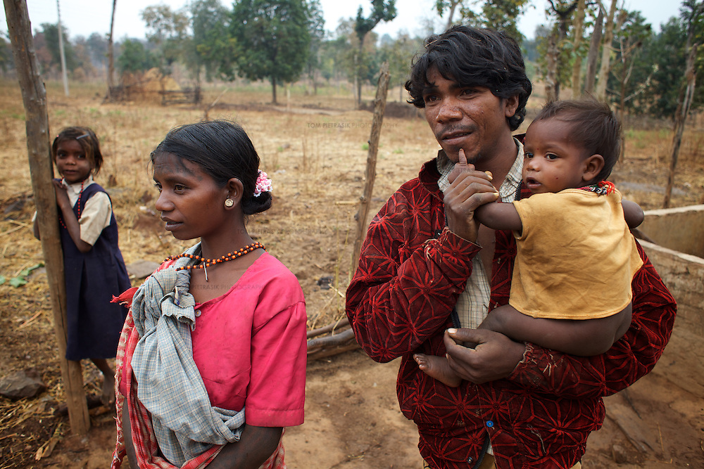 Ramlu Baiga (right) and Aghni Bai with son Shiv Kumar, 9 months, and daughter Bhagvati, 8, outside their home in Indripani.<br /> <br /> Ramlu Baiga, 33, and his wife Aghni Bai, 28, used to live in Bodhi Daldali which, since 2003, has been the location of a 668 hectare bauxite mine, run by Balco &amp; Vedanta (Vedanta is a UK headquartered company). When the mine was established adivasi (tribal) Ramlu Baiga and his family were told to move. The Rs.100,000 they received per acre of land they used to own did not properly compensate them for their loss as they had legal rights over only 2.5 acres of the 17.5 they cultivated. Furthermore, Ramlu has to share compensation with his four brothers with each ultimately only receiving Rs.50,000. The Bodhi Daldali mine directly employs just 70 people. 750 contractors, most of them casual day-wage workers, provide the labour without which the mine would not function. <br /> <br /> Photo: Tom Pietrasik<br /> Kawardha District, Chhattisgarh. India<br /> February 20th 2011