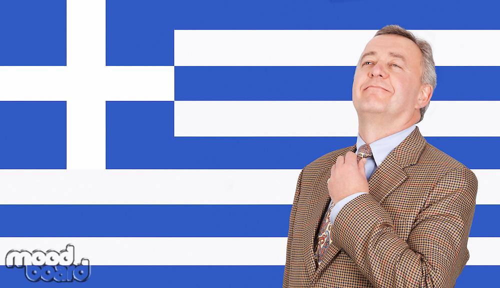 Middle-aged businessman adjusting necktie with pride over Greek flag