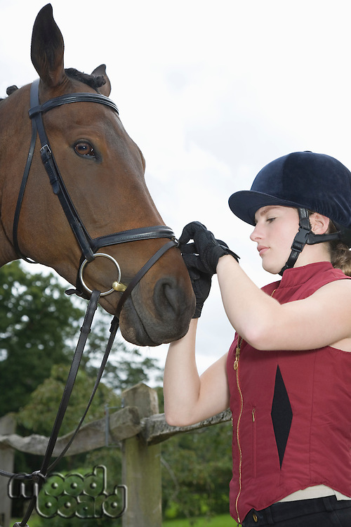 Girl tightening horse's bridle