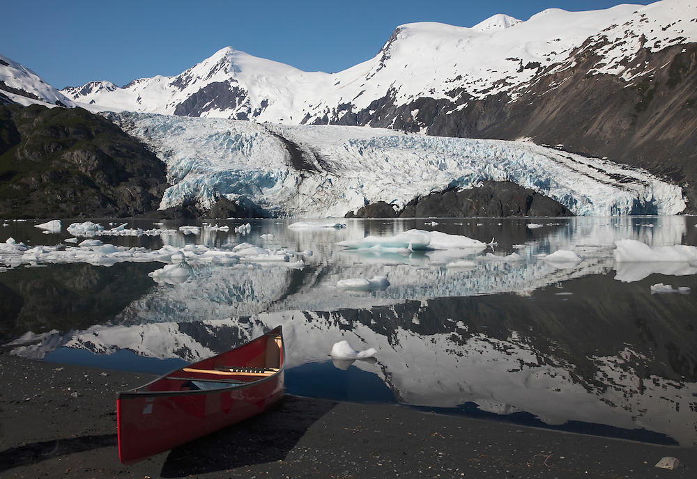 Alaska; Scenic morning view of Portage Glacier and reflection in Portage Lake with canoe, Chugach National Forest.