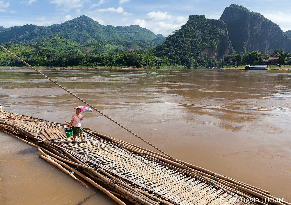 Woman walking on a small bamboo bridge leading to the Pak Ou caves.