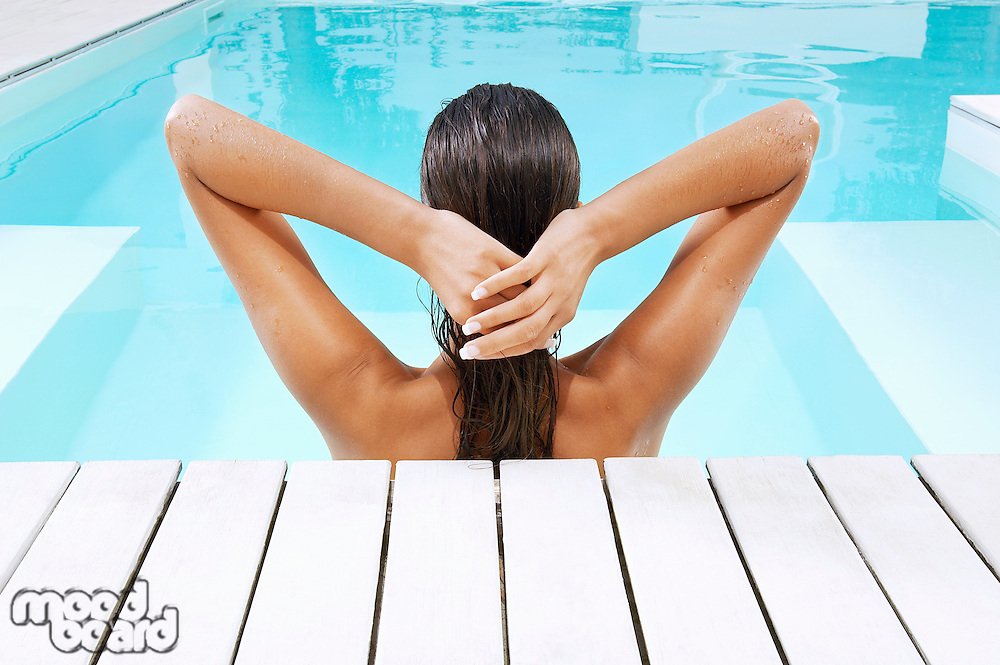 Young Woman in Swimming Pool at poolside pulling back hair back view