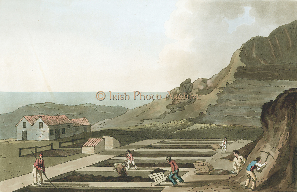 General view of an Alum works in the Whitby area.  From George Walker 'The Costume of Yorkshire' Leeds 1814, Aquatint. Steeping calcined (burnt) shale in water in pits produce raw alum liquor which would be gravity fed to processing plant where it would be refined and boiled until alum crystals produced. These were important as a mordant (fixer) in textile dyeing industry.