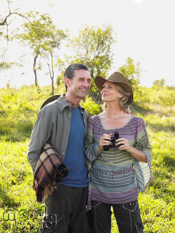 Adult couple outdoors man carrying blanket woman binoculars smiling