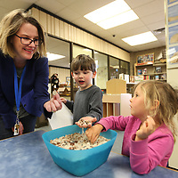 Grace Hall, Lee County Library children's librarian, shows a nickel she found to Nicholas Luker, 4, of Saltillo and Magnolia Reed, 4, of Tupelo, as they play the money hunt game after Children's storytime at the Library.