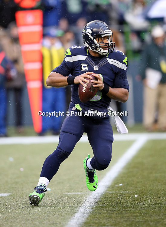 Seattle Seahawks quarterback Russell Wilson (3) rolls to his right while looking to pass in the first quarter during the 2015 NFL week 16 regular season football game against the St. Louis Rams on Sunday, Dec. 27, 2015 in Seattle. The Rams won the game 23-17. (©Paul Anthony Spinelli)