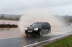 © Licensed to London News Pictures. 14/11/2019. Hereford, Herefordshire, UK. Motorists negotiate flooding on the A 4103 near Hereford. Very heavy rain overnight and today has caused roads to flood and rivers to burst their banks in Herefordshire, UK. Photo credit: Graham M. Lawrence/LNP