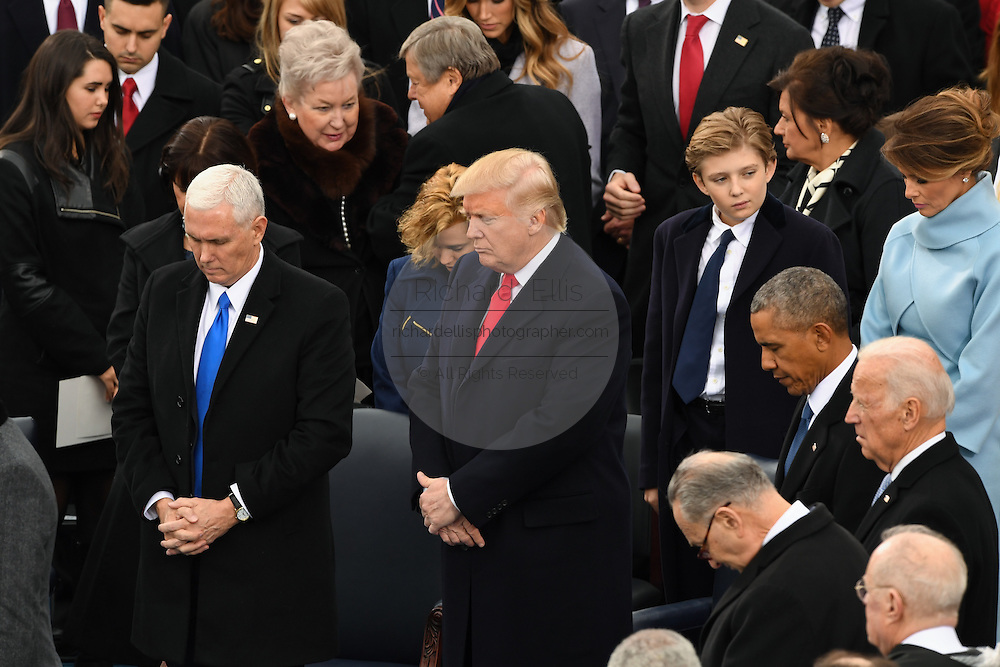 President Donald Trump and Vice President Mike Pence down their heads for prayer before becoming the 45th President of the United States of America during the Presidential Inauguration on Capitol Hill January 20, 2017 in Washington, DC.