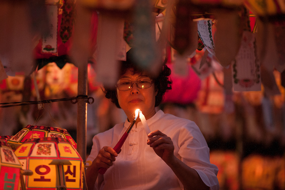 A woman lights a candle for a lantern during celebrations at Yongeun Temple in Busan, South Korea, May 28, 2012.