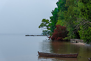 An old rowboat is tied up close to shore close to coroful trees with a pier in the distance.