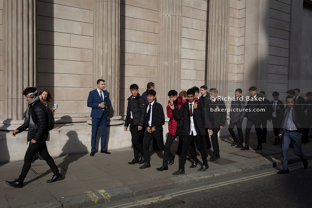 As visiting schoolboys walk past, a City businessman checks for messages and uses social media beneath the walls of the Bank of England, on 30th October 2017, Threadneedle Street, in the City of London, England.