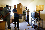 MILWAUKEE, WI — AUGUST 8, 2014: John Campbell with Eagle Moving and Storage Company, center, removes boxes from an evicted apartment at 714 West Galena Avenue in Milwaukee. The tenant was not present for the eviction.
