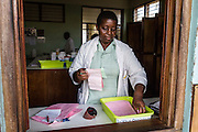 A pharmacist in the hospital pharmacy putting together prescriptions for a patient. St Walburg's Hospital, Nyangao. Lindi Region, Tanzania.