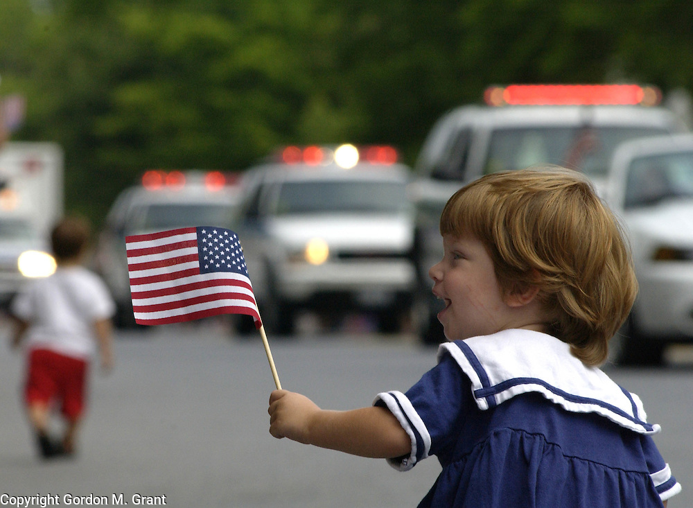 Southampton, NY - 070403 - Zoe Gelber of Atlanta, GA waves an American Flag during the July 4th parade in Southampton, NY Friday morning.   Gordon M. Grant Photo