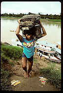 Men unload blocks of crude rubber from boat & carry them up river bank for processing at Eirunepe. Brazil