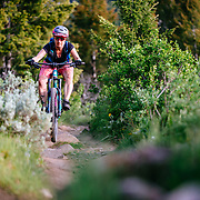 Heather Goodrich rides Singletrack above the town of Jackson, Wyoming at sunset.